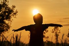 Азиатский ребенк играя в поле, чувствует свободным и хочет лететь для свободы стоковые фото
