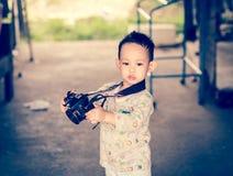 Азиатский ребенк принимает фото камерой DSLR Стоковое Изображение RF