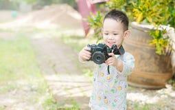 Азиатский ребенк принимает фото камерой DSLR Стоковое фото RF