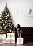 Азиатский ребенк ребёнка ребенка сидя под украшенной рождественской елкой золота с подарком заплатки золота представляет Стоковая Фотография