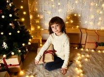 Азиатский ребенк ребёнка ребенка сидя под украшенной рождественской елкой золота с подарком заплатки золота представляет Стоковые Изображения