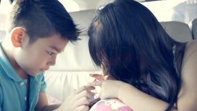 Азиатский ребенок играя умный телефон совместно в автомобиле