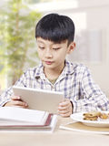 Азиатский ребенок используя планшет Стоковые Изображения RF
