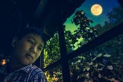 Азиатский ребенок сидя около окна и смотря в сторону пока чувствующ Стоковое Фото