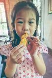 Азиатский ребенок усмехаясь и наслаждается съесть обвалянный в сухарях сыр s моццареллы Стоковое Изображение RF