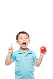 Азиатский ребёнок держа и есть красное яблоко, изолированное на белизне Стоковая Фотография RF