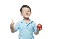Азиатский ребёнок держа и есть красное яблоко, изолированное на белизне Стоковое Изображение
