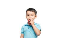 Азиатский ребёнок держа и есть красное яблоко, изолированное на белизне Стоковое Фото