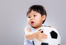 Азиатский ребёнок держа футбольный мяч Стоковые Изображения