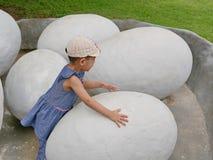 Азиатский ребёнок касаясь яичку динозавра для того чтобы исследовать если она чувствует что-нибудь внутрь стоковое изображение rf