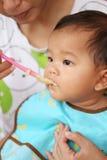 Азиатский ребёнок к еде еды в концепции здоровых ед и гайки Стоковая Фотография