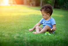 Азиатский ребёнок сидя в зеленой природе Стоковая Фотография RF