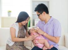 Азиатский родитель нянча их младенца стоковое изображение rf