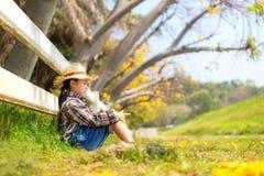 Азиатский сидеть девушки ребенк на открытом воздухе в упаденных листьях на осени в парке, счастливый и ослабить в летнем времени стоковая фотография rf