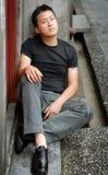 азиатский сиротливый человек видит для того чтобы сидеть Стоковые Фото