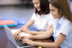 Азиатский студент в тайском mske университета домашняя работа в библиотеке Стоковое Фото