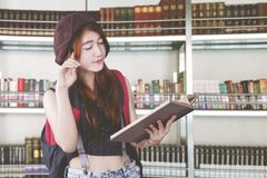 Азиатский студент уча в библиотеке стоковое фото rf