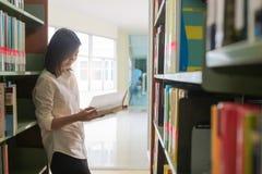 Азиатский студент читая книгу в библиотеке Стоковое Изображение RF