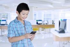 Азиатский студент preteen используя smartphone стоковое фото