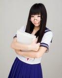 Азиатский студент девушки в школьной форме с книгой Стоковые Изображения RF