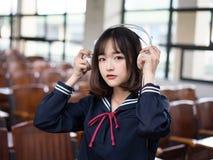 Азиатский студент девушки в школьной форме уча в классе Стоковые Изображения RF