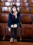 Азиатский студент девушки в школьной форме уча в классе стоковые фото
