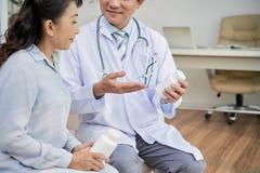 Азиатский терпеливый говорить к доктору стоковые изображения rf