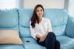 Азиатский усмехаться женщин счастливый для релаксации на софе дома стоковое фото rf
