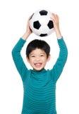 Азиатский футбольный мяч повышения мальчика вверх стоковое изображение rf