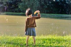 Азиатский ход маленькой девочки лист к озеру пока восхищает nat стоковые изображения