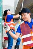 Азиатский художник с щеткой и краска на строительной площадке Стоковые Фотографии RF