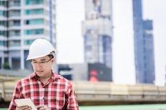 Азиатский человек дела и инженера с красной рубашкой Скотта имеет plannin стоковая фотография rf
