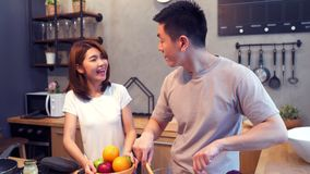 Азиатский человек подготавливает еду салата в кухне Красивые счастливые азиатские пары варят в кухне акции видеоматериалы