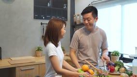 Азиатский человек подготавливает еду салата в кухне Красивые счастливые азиатские пары варят в кухне сток-видео