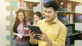 Азиатский человек подростка читает таблетку с девушками говорит на шиканье Стоковая Фотография RF