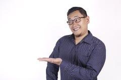 Азиатский человек представляя что-то на его стороне с космосом экземпляра стоковое изображение