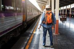 Азиатский человек путешественника при пожитки ждать перемещение поездом на вокзале Чиангмая, Таиланде стоковое фото rf