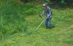 Азиатский человек режа траву используя резец щетки бензина стоковые фото