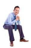 Азиатский человек сидя на прозрачном стуле Стоковые Фото
