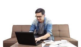 Азиатский человек усмехаясь и используя ноутбук для работы или sufing интернет стоковое изображение