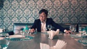 Азиатский человек в бизнесмене костюма ждать в кафе их еду Длинные ожидания для приказывать слабонервно акции видеоматериалы