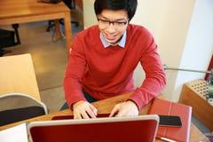 Азиатский человек в деятельности стекел на компьтер-книжке стоковая фотография rf