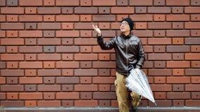 Азиатский человек в куртке Брайна с ясным зонтиком Стоковое фото RF
