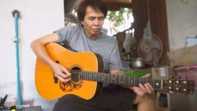Азиатский человек играя гитару, Таиланд - 16-ое августа 2017 сток-видео