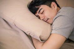 Азиатский человек кладя на кровать, глубокую в сне стоковые изображения rf