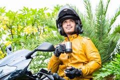 Азиатский человек на мотоцикле с шлемом Стоковое Изображение
