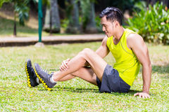 Азиатский человек протягивая в тренировке фитнеса Стоковые Изображения