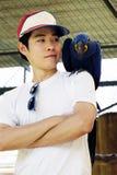 Азиатский человек с красивым попугаем ары гиацинта Стоковая Фотография