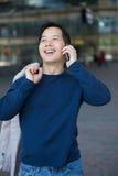 Азиатский человек усмехаясь с мобильным телефоном стоковое изображение rf