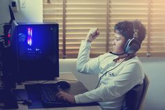 Азиатский gamer мальчика играя игры на компьютере в комнате дома, нося наушники и используя подсвеченную красочную клавиатуру стоковые фото